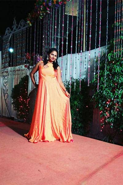 Vinita, a boutique customer, is wearing a peach color gown at a marriage function