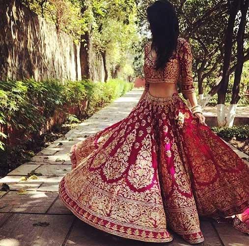 A fair skin tone bride wearing a bright colour lehenga blouse