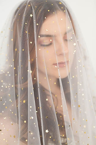 a white veil embellished with light coloured stars and similar adornments