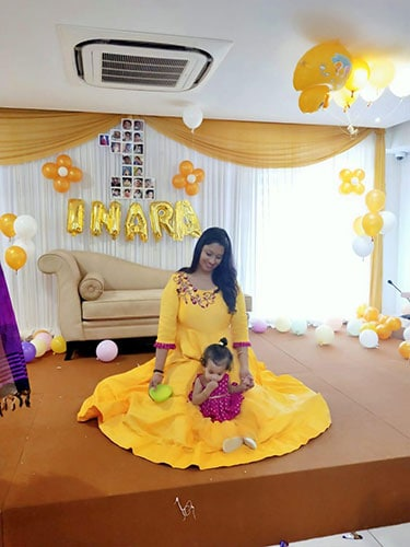 One year girl wearing a yellow frock matching with her mothers gown dress