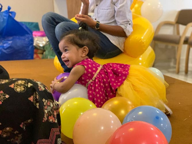 One year old girl Inara wearing a blouse & skirt dress design from the boutique