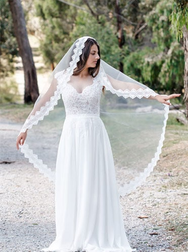 White gown paired with a Veil edged with a scalloped lace