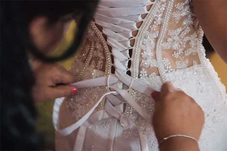 A designer ties the back bands of a wedding dress