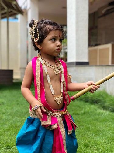 bare chested young boy with ornaments, a flute & a dhoti tied on his waist