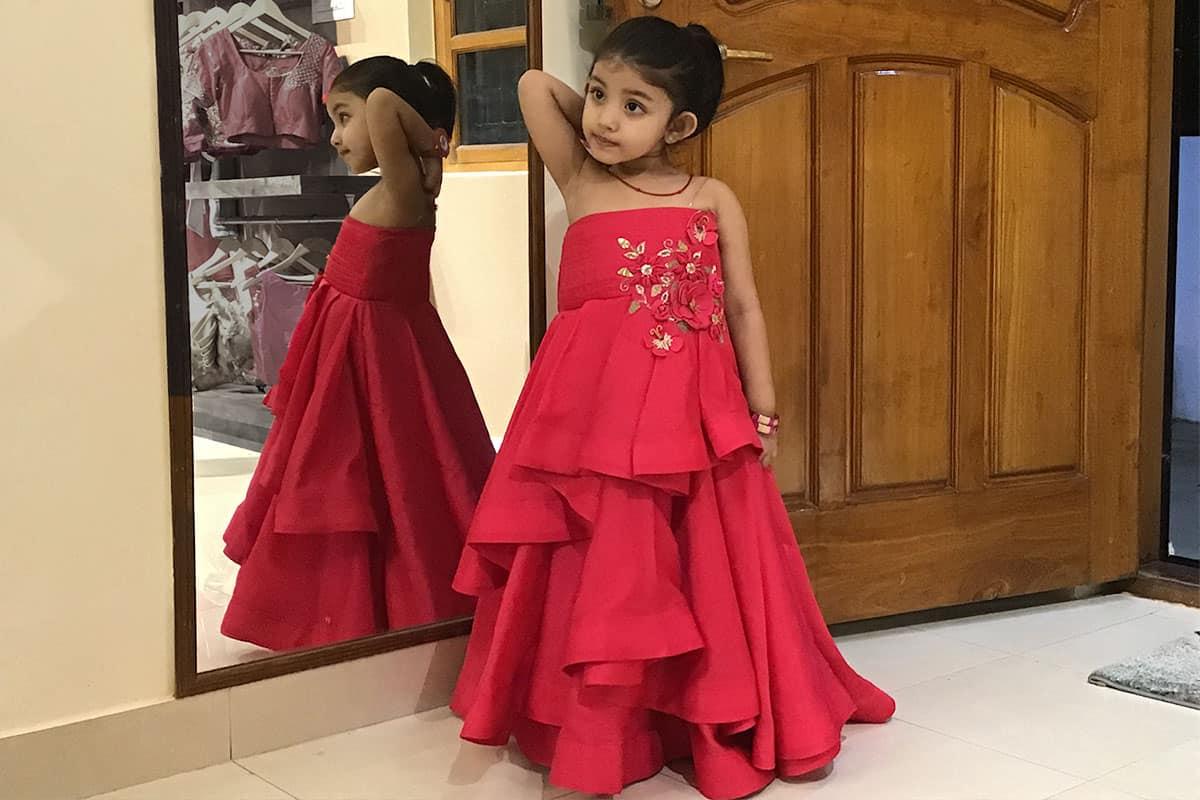 A red asymmetric hem kids gown dress with a bandeau shoulder