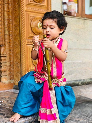 kid dressed in peacock blue dhoti and a pink shalya. Playing with a flute