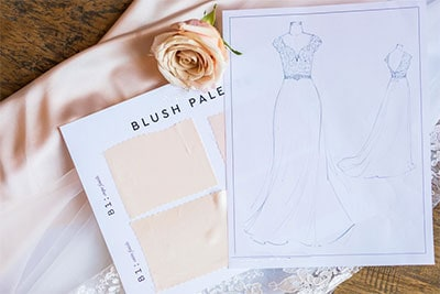 Gown design being matched with blush pale fabric swatch