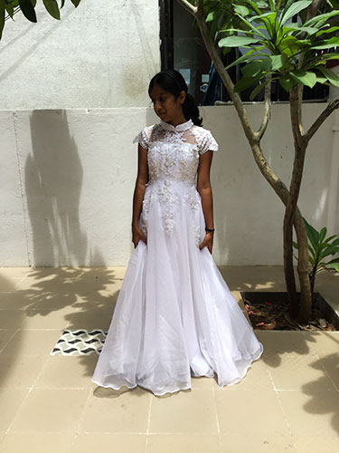White gown dress worn by Teenager Alwina who is posing against a white background