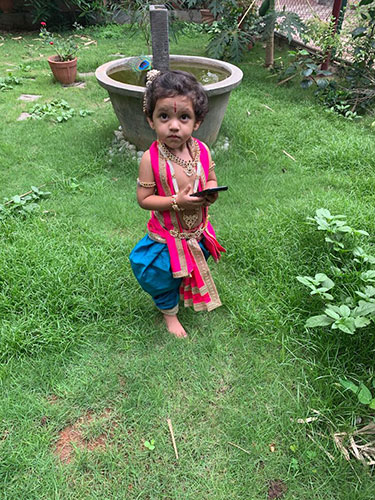 Young kid fully dressed up as Lord Krishna in a stole & dhoti and a peacock feather around his hairs