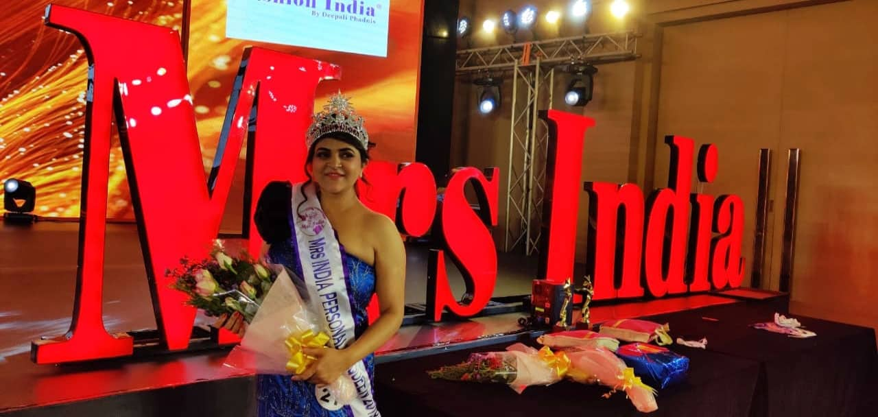 Mrs India Personality queen 2019 poses in front of the grand emblem of the event