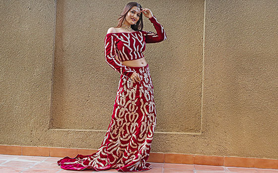 Lehenga blouse design in maroon. The lehenga skirt dons a train and is paired with a modern off shoulder full sleeve blouse