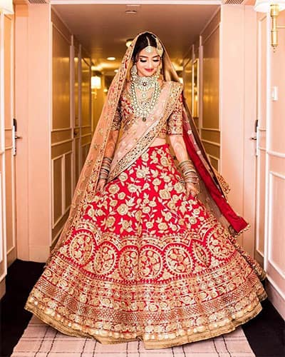 A bride wearing an A-line silhouette lehenga skirt in red which is paired with same color blouse and a lighter peach colored dupatta