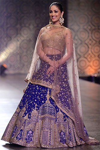 bollywood actress Yami Gautam dons a blue lehenga skirt that has a mosque like structure embellished through intricate embroidery