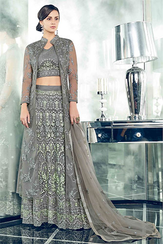 A dark grey colour lehenga skirt paired with a full sleeve blouse in same colour and a matching jacket attached to the dress