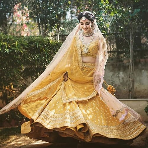 A bright mustard colour lehenga blouse and dupatta set for daytime marriage event
