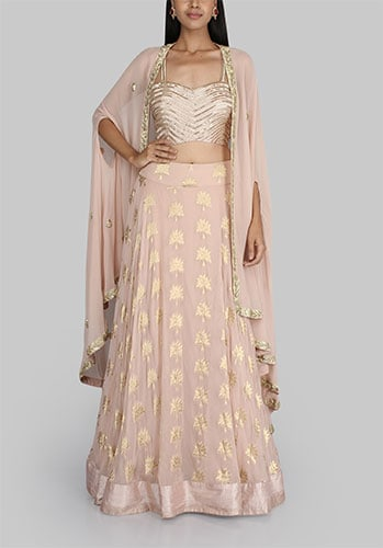 A peach colour cape in transparent net attached to a golden blouse paired with a peach colour lehenga
