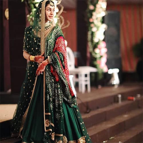 a dark green lehenga skirt paired with a simple blouse but a heavily embellished dupatta