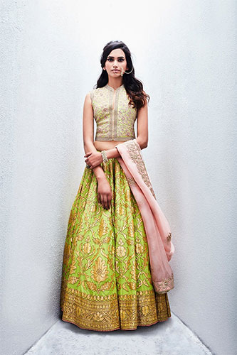 A sleeveless crop top blouse paired with a contrast lehenga skirt & a lighter hue of dupatta