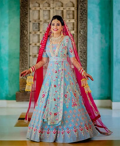 A light blouse lehenga blouse is styled with a same colour belt