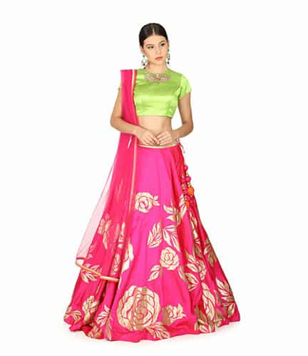 a green blouse contrasts the pink colour of the lehenga skirt & the dupatta