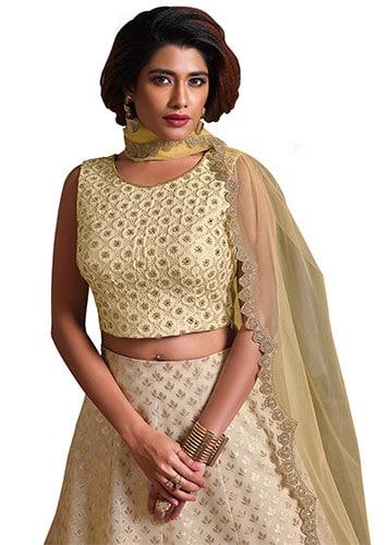 a beige colour lehenga blouse design with a plain dupatta that has scalloped border