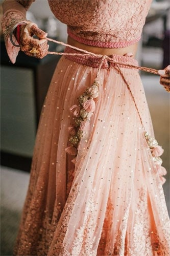 A bride tying the knots of her pink colour lehenga skirt
